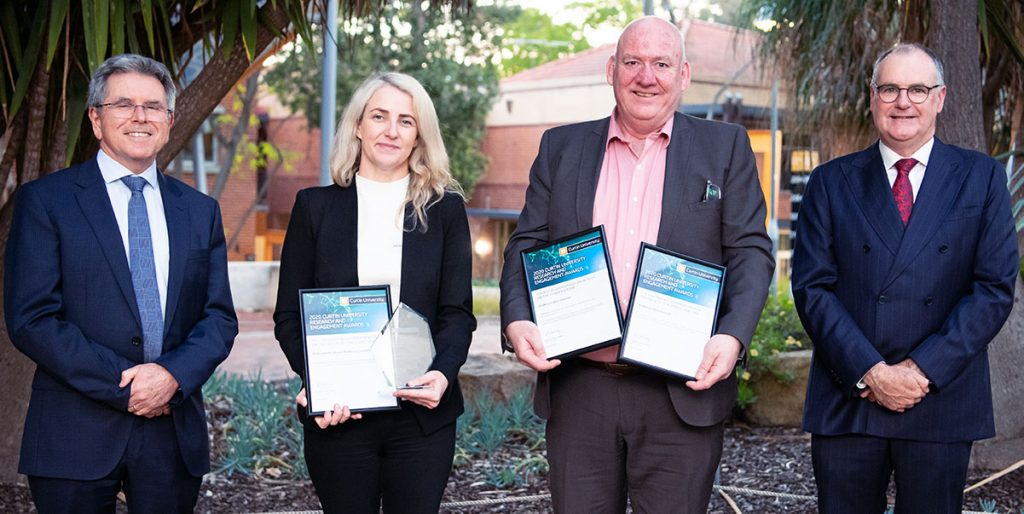 Four people standing outside, holding awards in their hands.