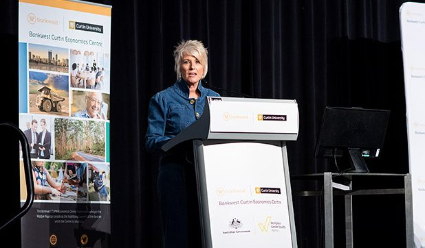 Libby Lyons talking on stage at a lectern with a BCEC pull up banner behind her
